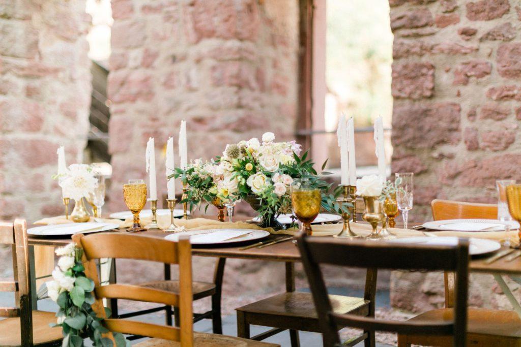 sommerliche Hochzeitsinspiration auf Burg Wertheim Hochzeit Tischdekoration mit vintage Mobiliar und Kerzen von One fancy fox