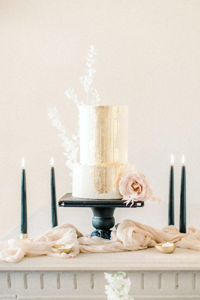 Ewigmein Fine Art Hochzeitsfotografie Hochzeit Hochzeitstorte mit Goldplättchen schwarzen Kerzen Rosen minimalistisch stilvoll
