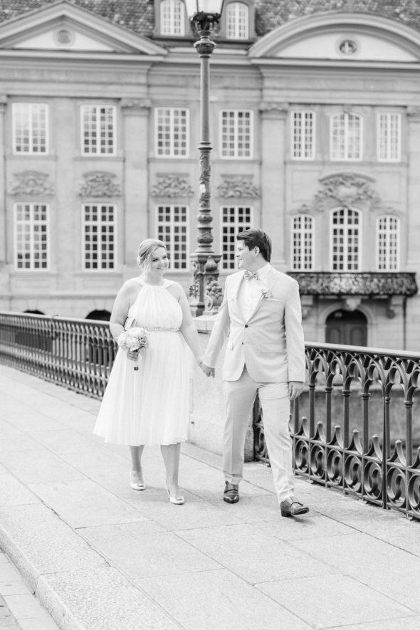 Braut in manolo blahnik Schuhen und Bräutigam laufen über die Münsterbrücke in Zürich, Schweiz